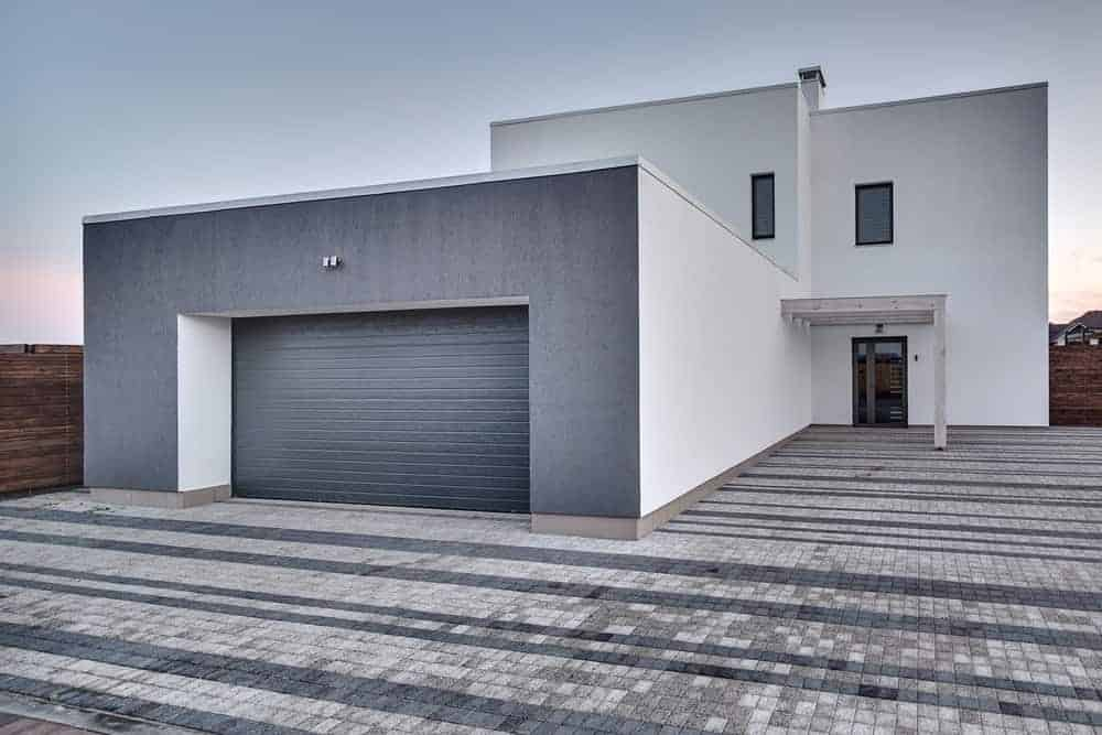 House with grey exterior featuring cube-tiles ground a garage.