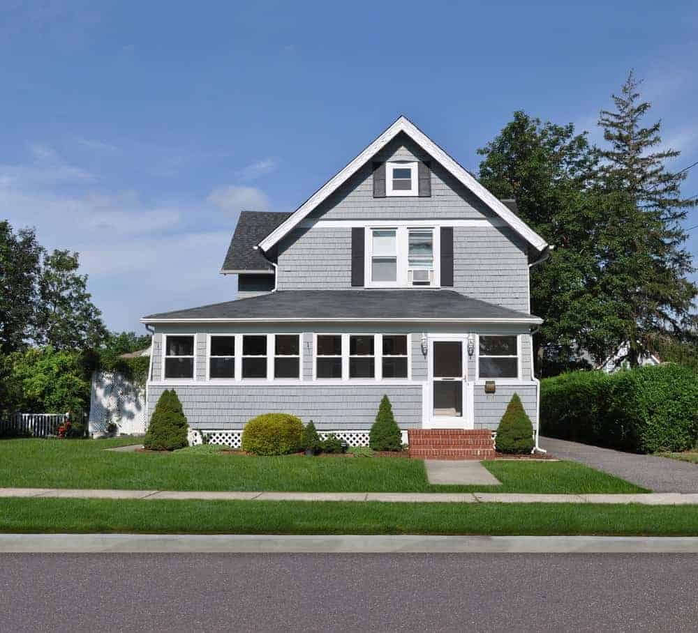 House with grey exterior and healthy frontyard lawn along with beautiful plants.