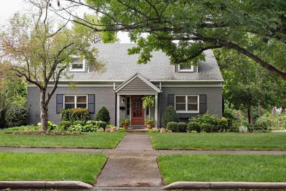 House with grey exterior and beautiful frontyard garden featuring healthy plants and lawn.