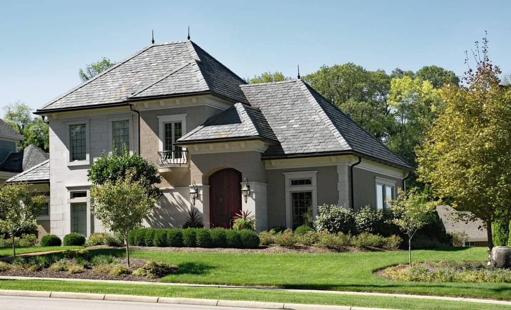 Two-storey house with grey exterior and beautiful frontyard garden.