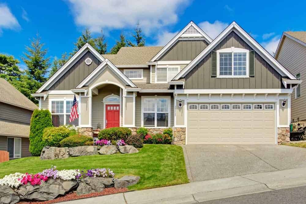 Two-storey house with grey exterior and beautiful frontyard garden along with a garage.