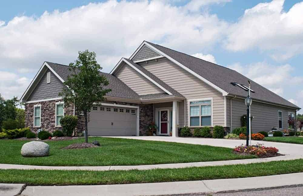 Bungalow house with grey exterior and a driveway along with a beautiful frontyard garden.