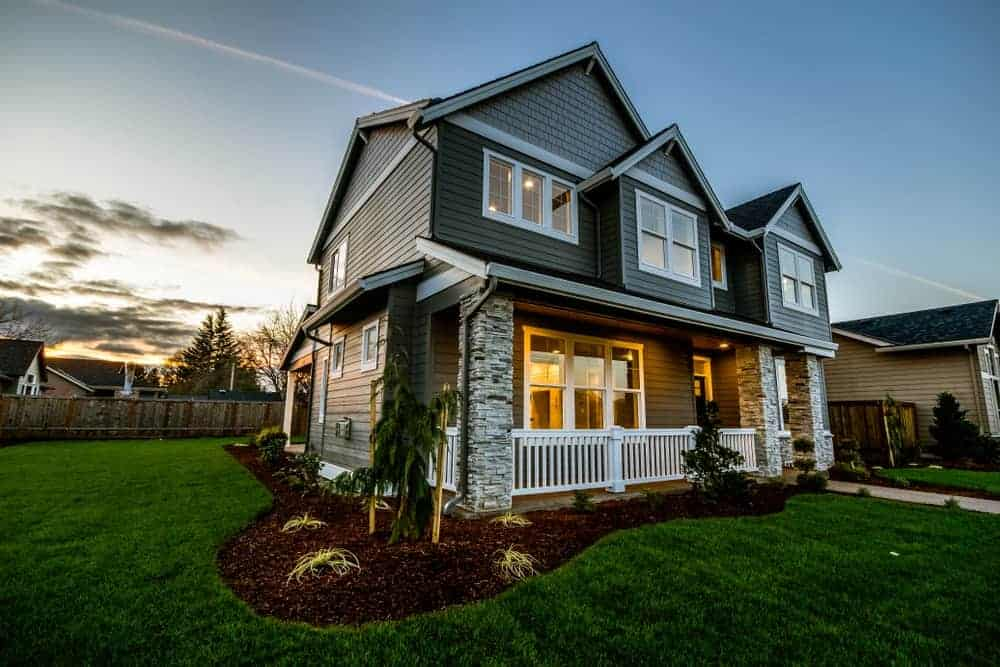 House with grey exterior and a porch featuring its beautiful and well-maintained lawn and garden area.