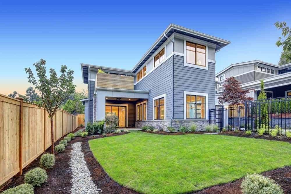 Two-storey house with grey exterior and beautiful garden featuring its well-maintained lawn and plants.