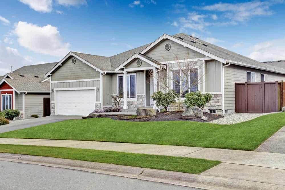 Bungalow house with grey exterior featuring a beautiful lawn.
