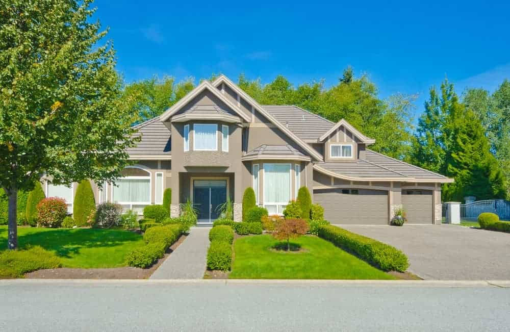 Large house with grey exterior and beautiful frontyard garden and garage.