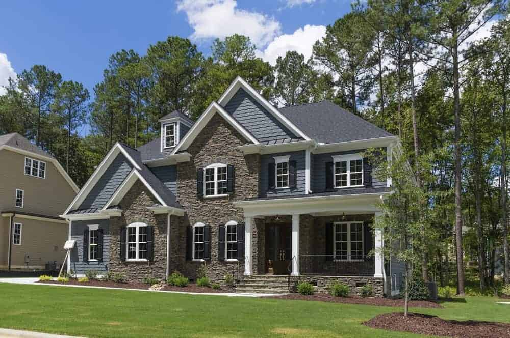 House with grey exterior and a porch surrounded by tall mature trees along with beautiful lawn and plants.