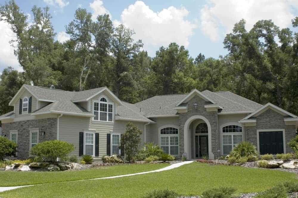 Large house with grey exterior featuring vast area of frontyard garden with beautiful plants, trees and lawn.