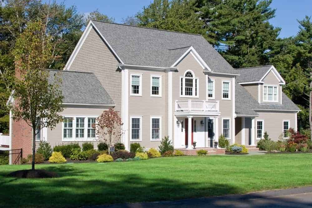 Large house with grey exterior and wide frontyard garden featuring wide-area lawn, beautiful plants and trees.