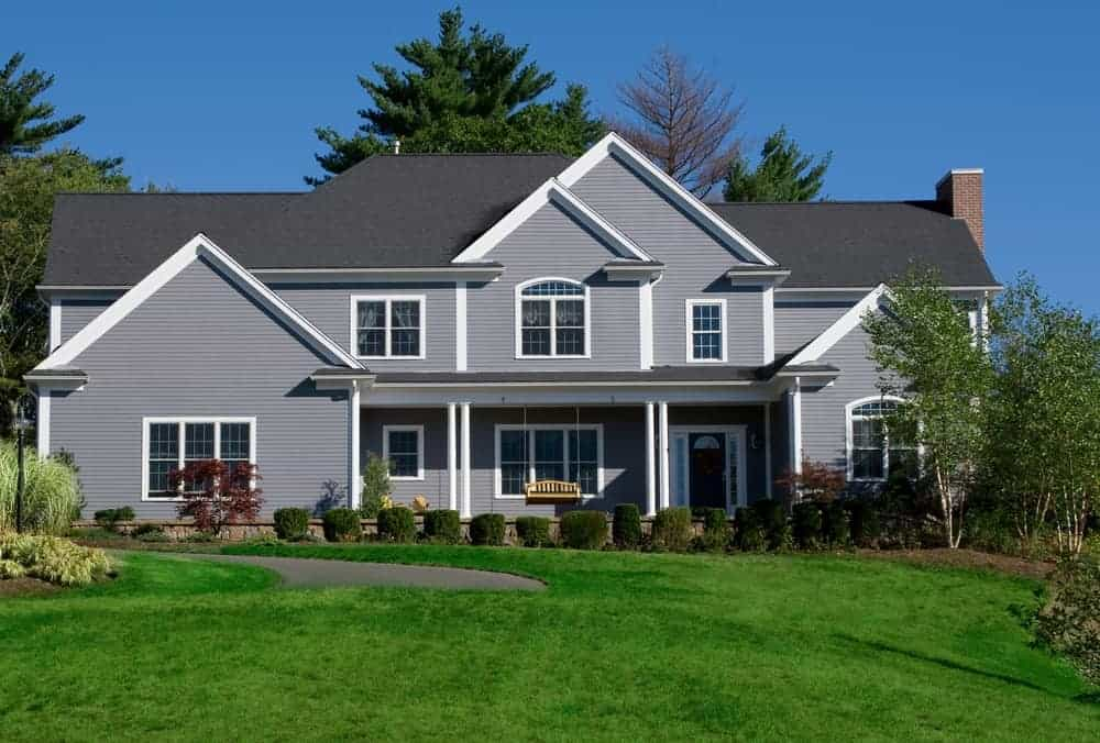 Large house with grey exterior and a walkway along with a beautiful frontyard garden featuring beautiful lawn, plants and trees.