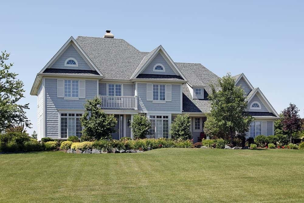Large house with grey exterior and a terrace along with a huge frontyard garden area featuring a beautiful lawn, plants and trees.