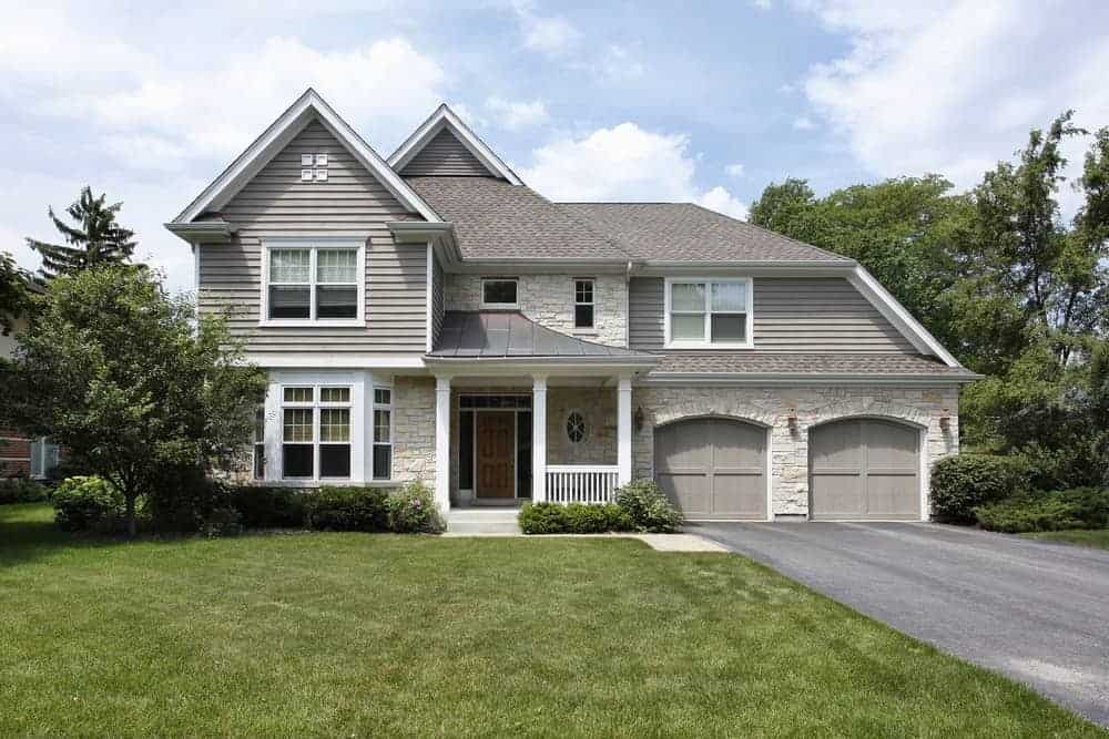 Large house with grey exterior and a small porch along with a garage and well-maintained lawn, plants and trees.