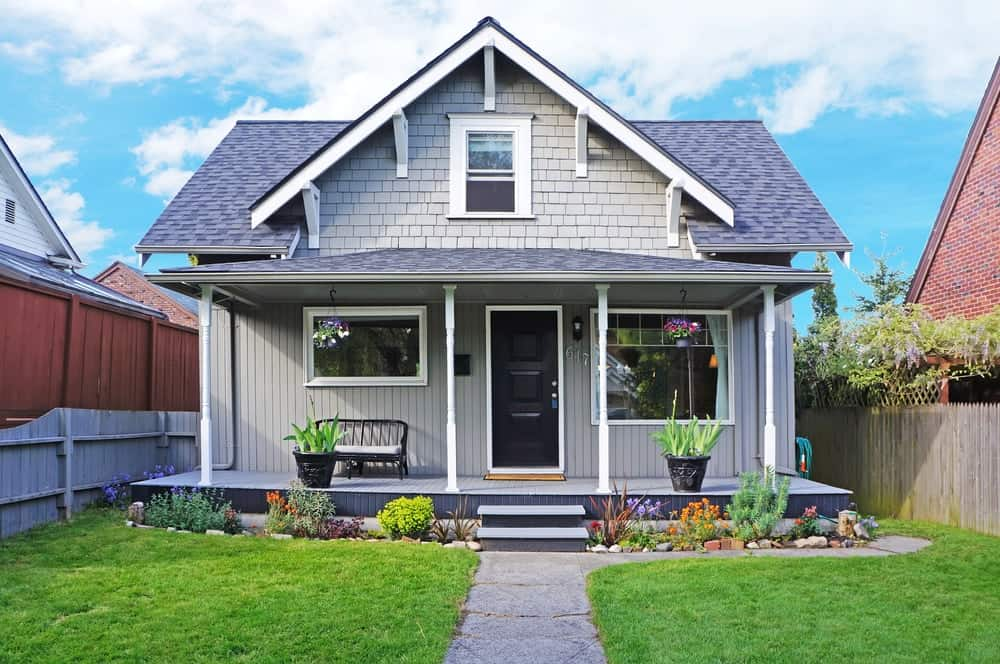 House with grey exterior and porch along with green lawn and colorful plants.