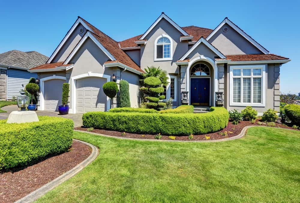 Beautiful house with extremely beautiful frontyard garden area featuring beautiful lawn, plants, trees and walkway.