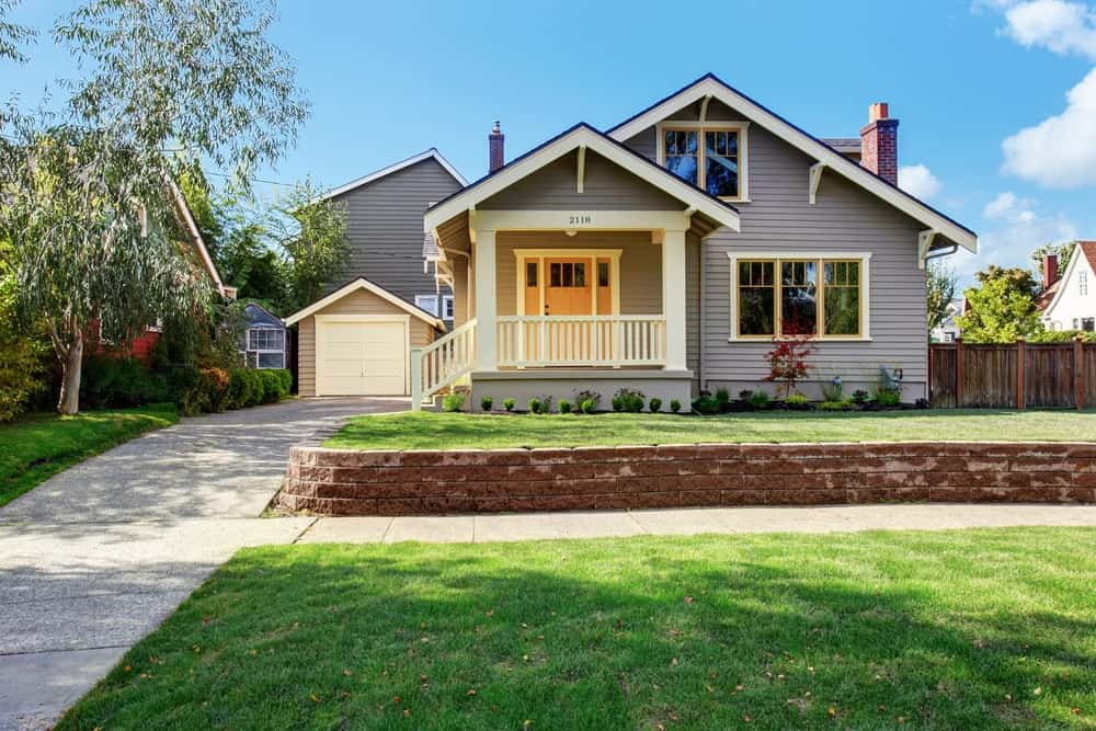 House with grey exterior and wide frontyard garden with well-maintained lawn and plants.