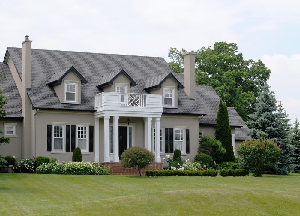 Large house with grey exterior and huge frontyard garden area featuring beautiful plants, trees and well-maintained lawn.