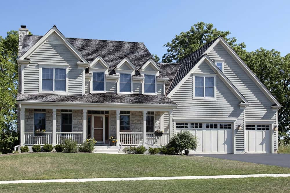 Large house with grey exterior showcasing a porch, garage and wide lawn frontyard.