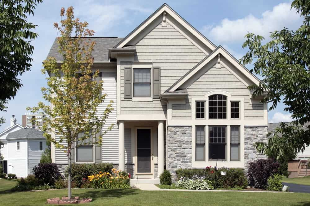 House with grey exterior and beautiful frontyard garden featuring beautiful plants and trees.