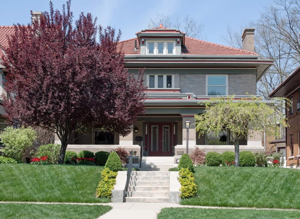 House with grey exterior featuring its beautiful trees, plants and lawn.