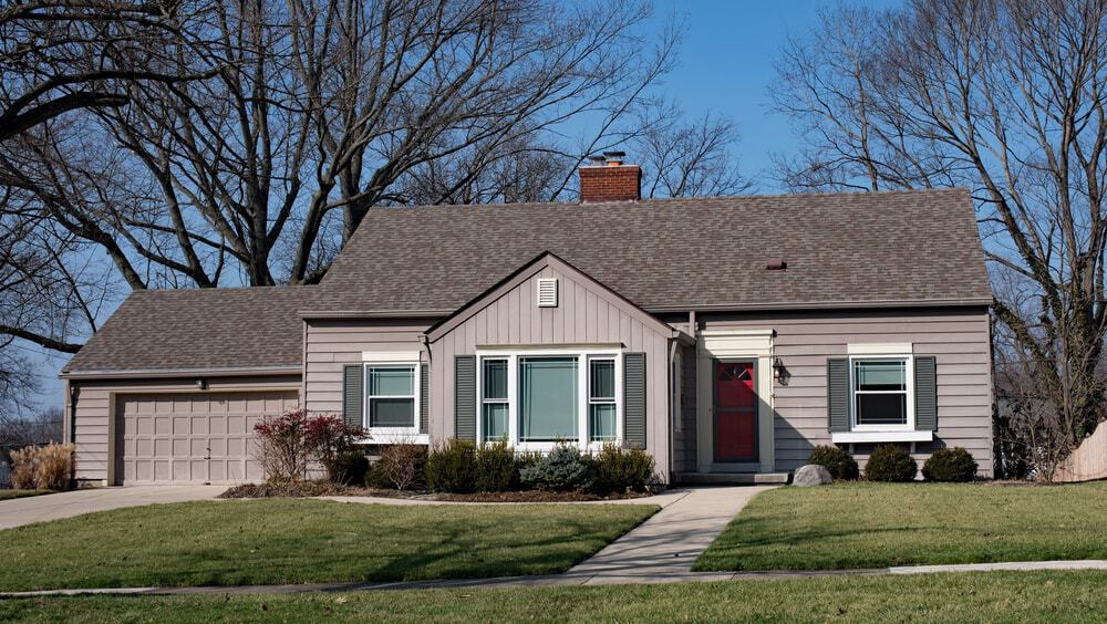 Bungalow-style house with grey exterior featuring a garage and wide garden area.