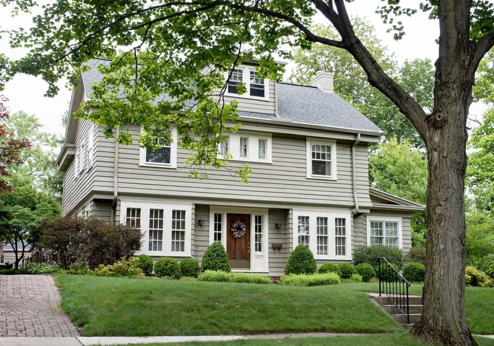 Large house with grey exterior and beautiful garden featuring green plants, lawn and trees.