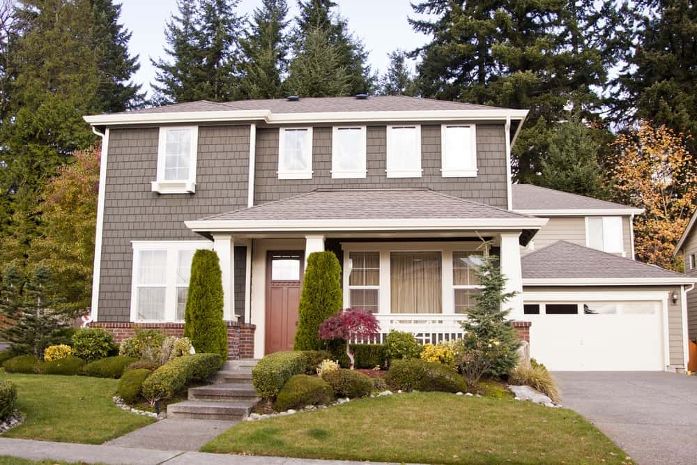 Large house with grey exterior showcasing its beautiful garden plants, trees, lawn and garage.