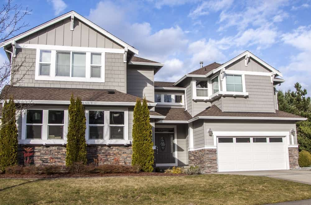 Large house with grey exterior featuring its frontyard garden with beautiful plants and lawn along with its garage.