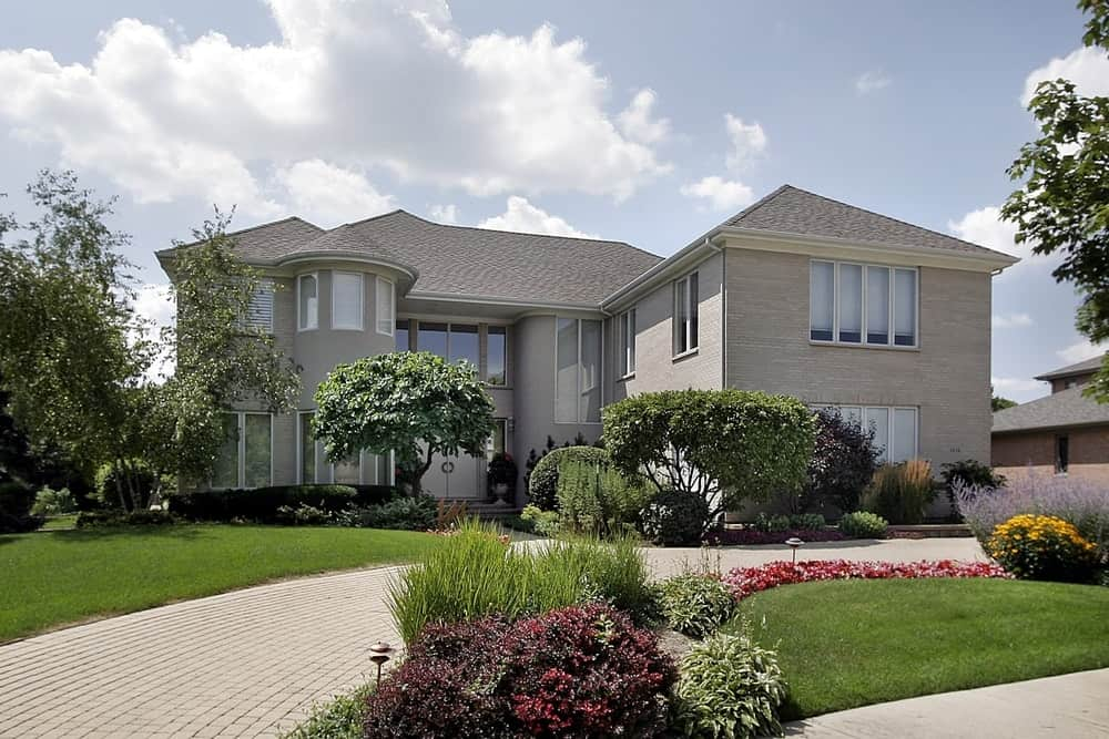 Large house with grey exterior featuring a beautiful walkway and garden with plants, trees and lawn on side.