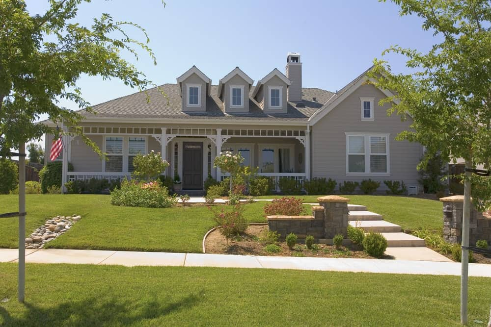 Large house with grey exterior featuring its wide frontyard garden with beautiful lawn, colourful plants and trees.