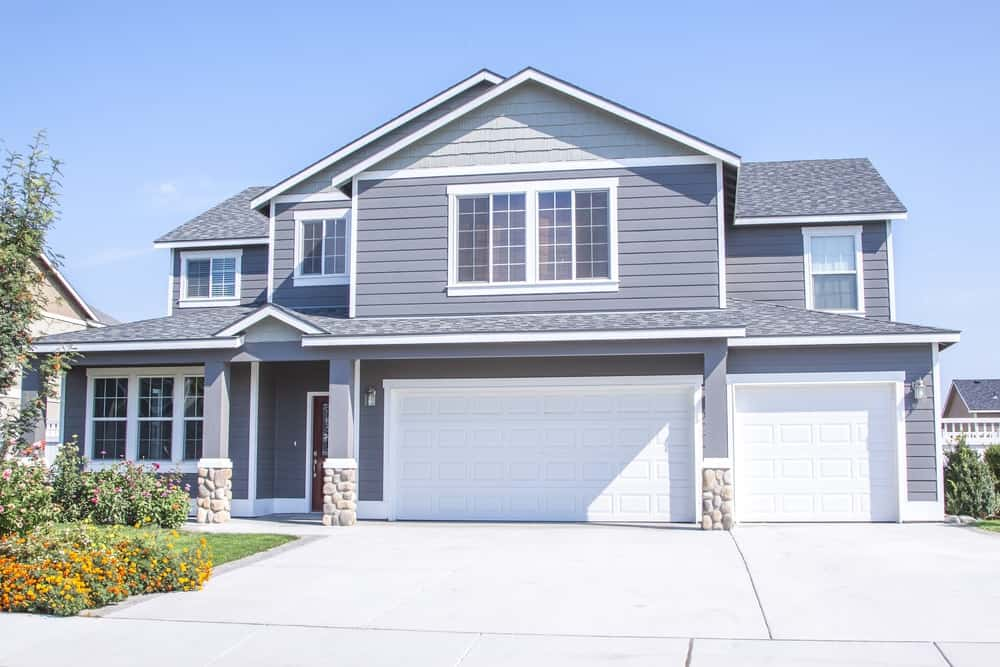Large house with grey exterior featuring its large garage and garden on side.