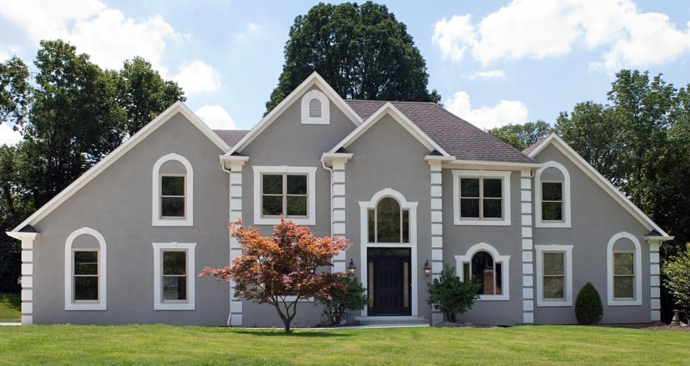 Gray stucco house with white trims, pitched roofs, and arched windows.