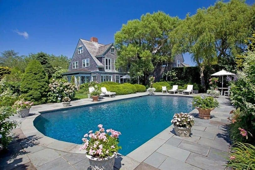 This house boasts a large outdoor area with a beautiful garden and a swimming pool surrounded by plants and flowers.