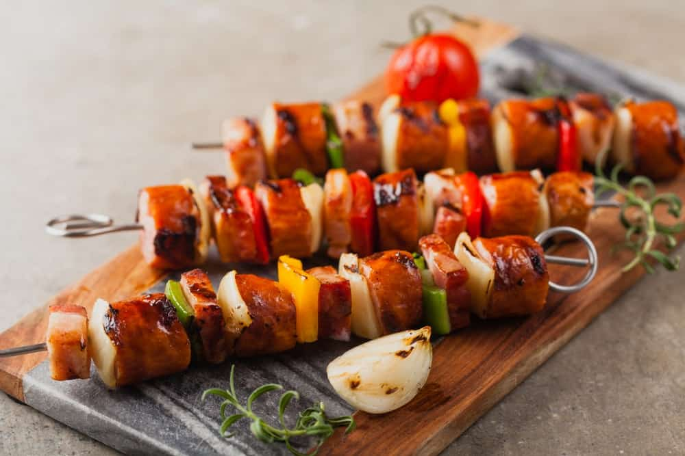 Grilled skewers with beef, bacon, and vegetables on wooden board.