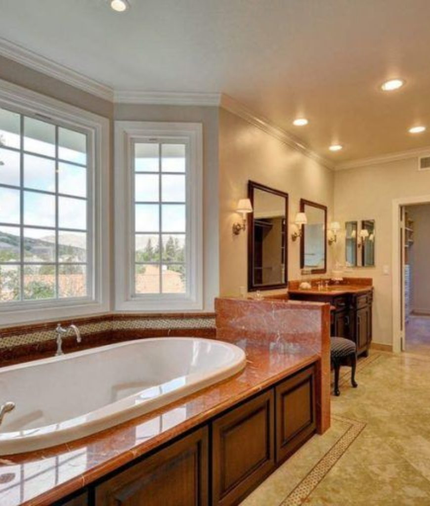 The bathroom features well-placed lighting and a bathtub.