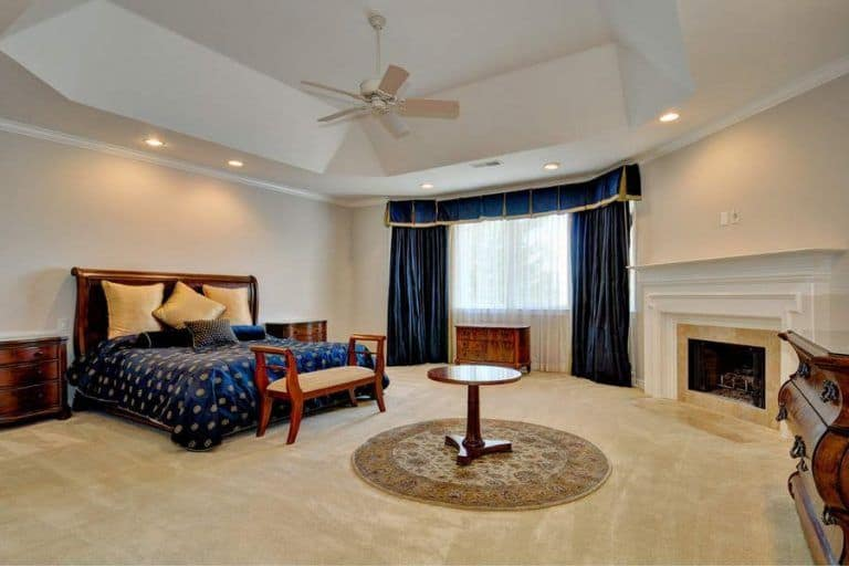 The bedroom boasts a large bed and a fireplace along with a carpet flooring.