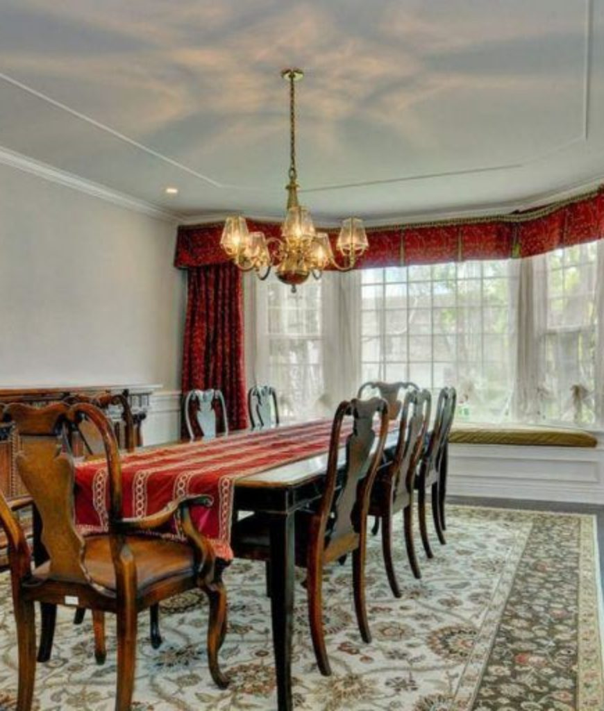 The dining room boasts an elegant vibe with its red velvet curtains and tablecloth along with a hardwood flooring with a rug.