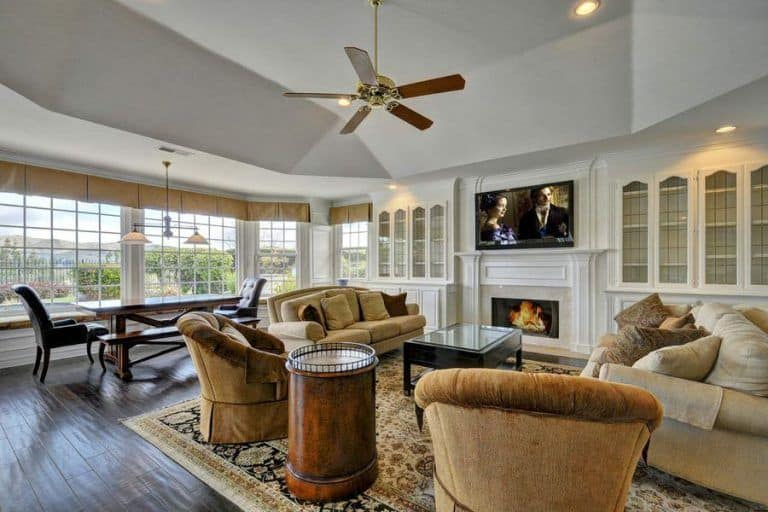 An open living room with tan sectionals and round back chairs facing the television above the modern fireplace.