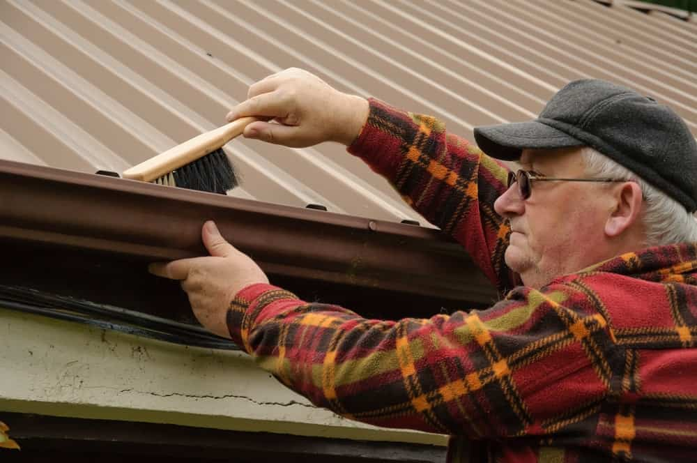 The man is using a cleaning brush with white and black bristles to remove dirt from the gutter.