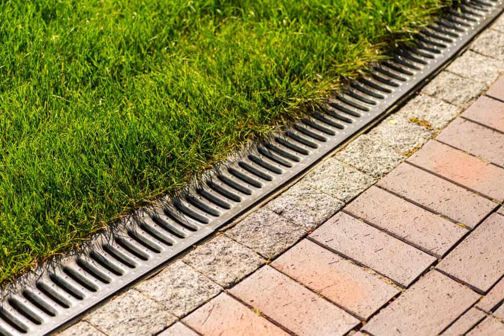 A metal gutter separating the lawn from the walkway.
