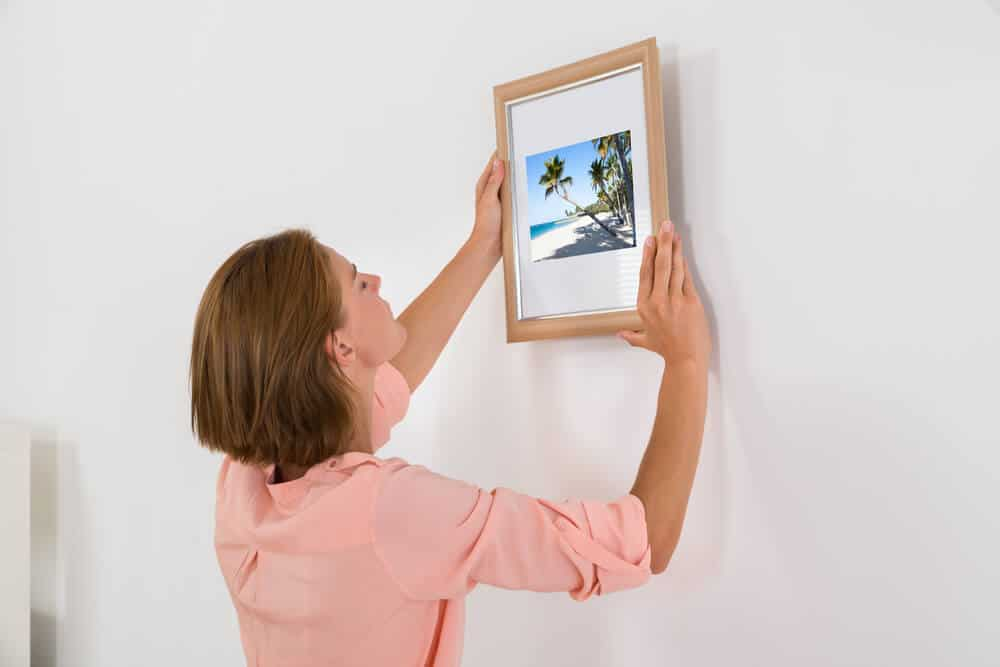 A woman hanging a wooden picture frame on the wall.