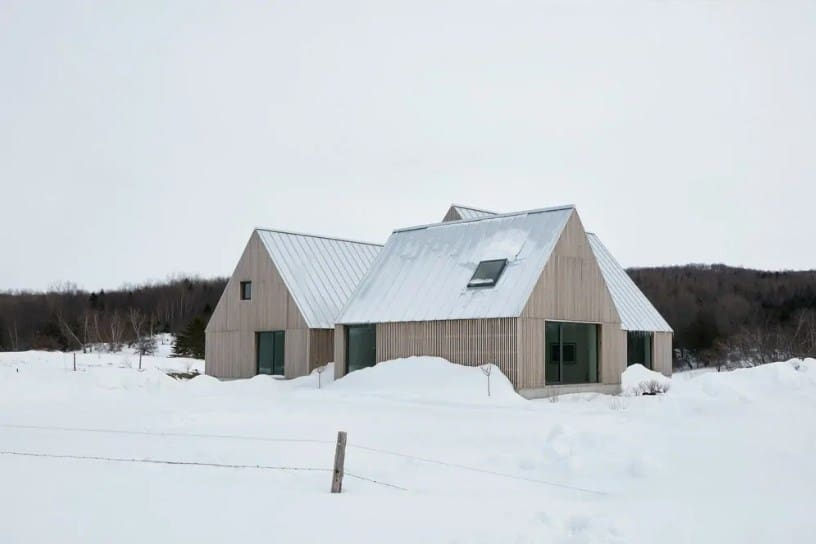 This house boasts wooden exterior and a vaulted roof. Its surroundings are covered in snow.