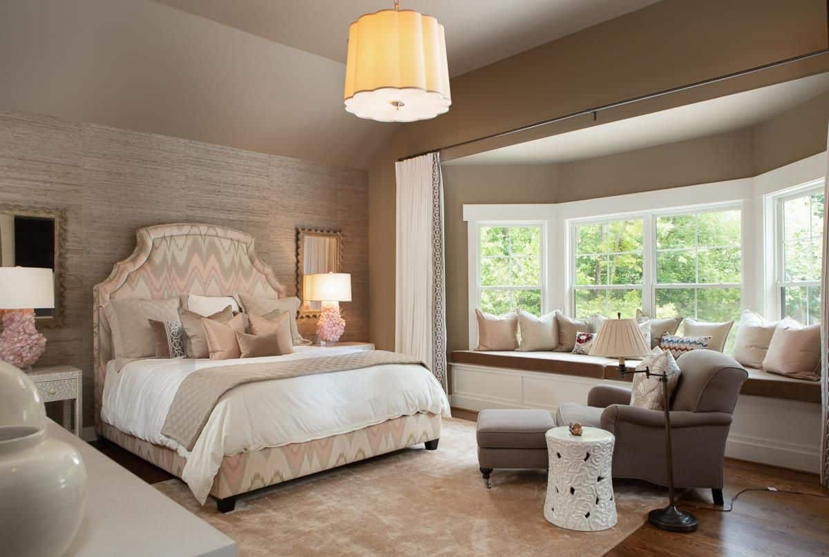 Glamorous primary bedroom boasts a pink patterned bed and gray chaise lounge over a velvet rug. It has window seat nook fitted with a brown cushion and filled with neutral color throw pillows.