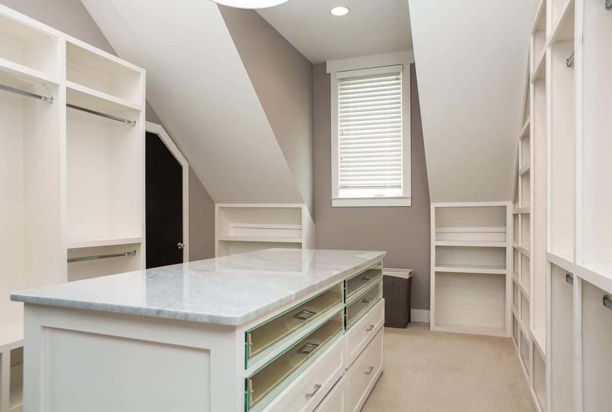 The home's closet features a large center island and multiple cabinetry.
