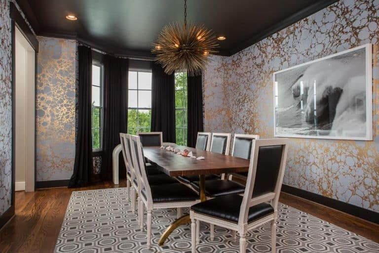 Black dining room clad in classy wallpaper boasts a rectangular dining table and black leather chairs that sit on a patterned rug. It is lighted by a unique pendant and recessed ceiling lights.