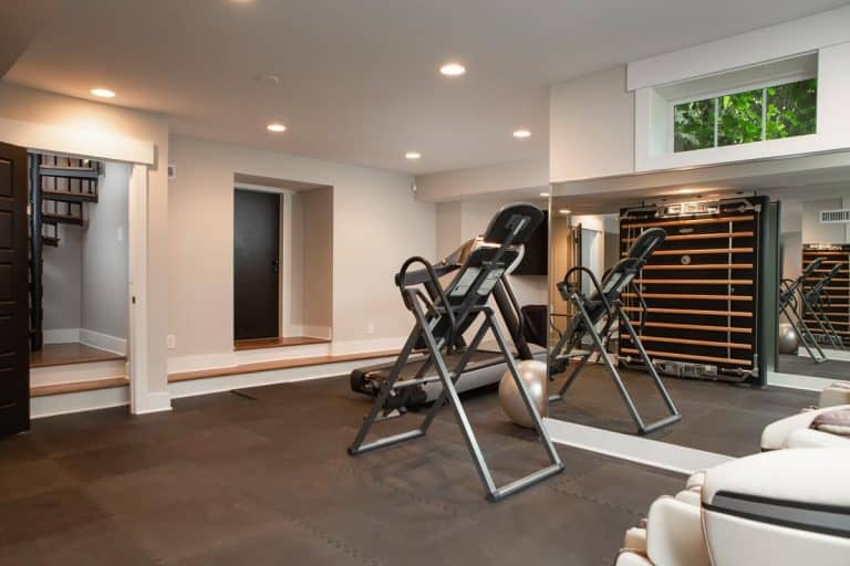 There's also a home gym inside the house lighted by recessed ceiling lights and surrounded by white walls.