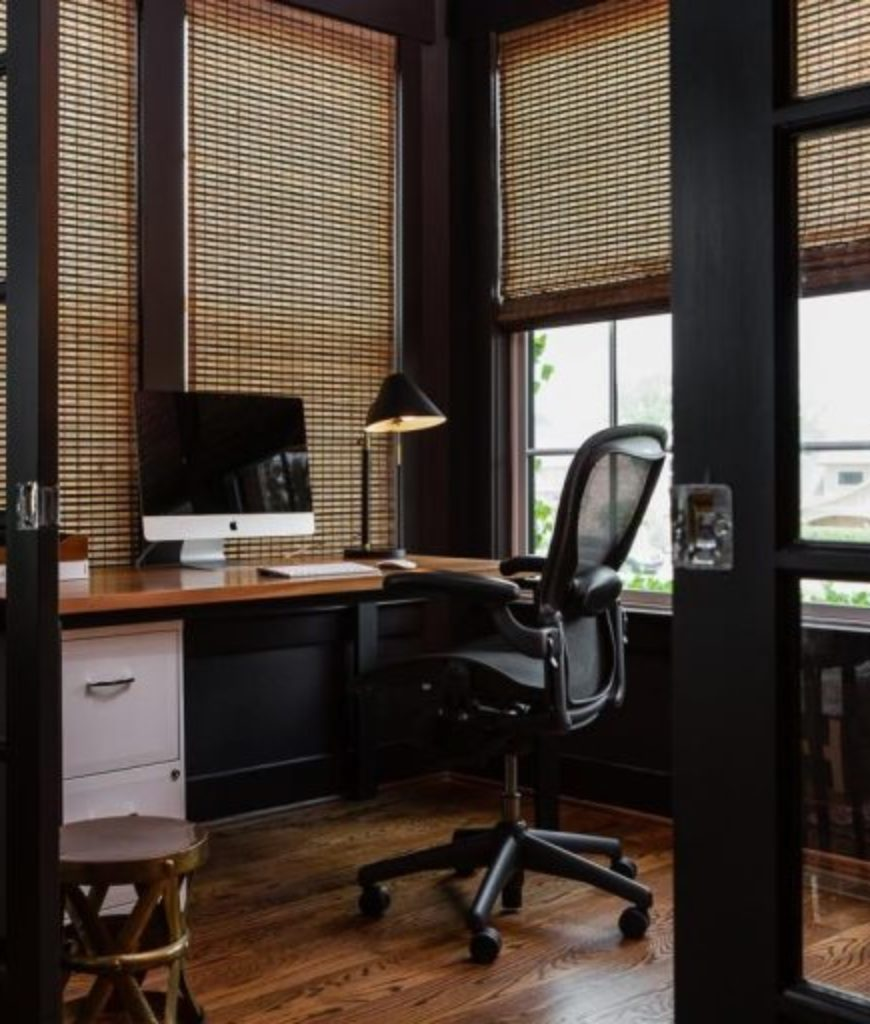 The home office looks elegant with its vinyl flooring, stylish window blinds and working desk.