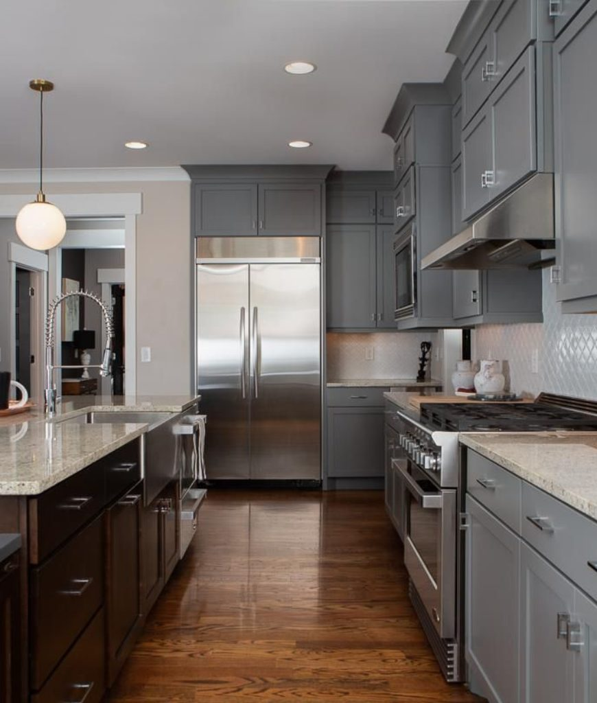 The kitchen features a large center island with a smooth marble countertop along with gray cabinetry and beautiful lighting.
