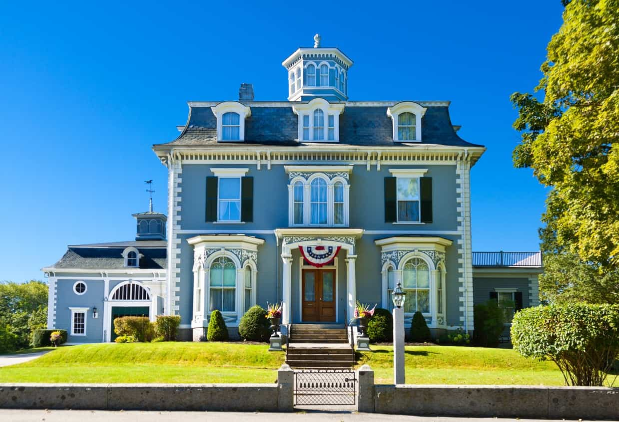 This historic house stands tall and proud against a backdrop of a clear blue sky and a green manicured landscape. White trims emphasize architectural details while the one-toned blue exterior for both stories of the house makes it look taller and unapologetically regal.