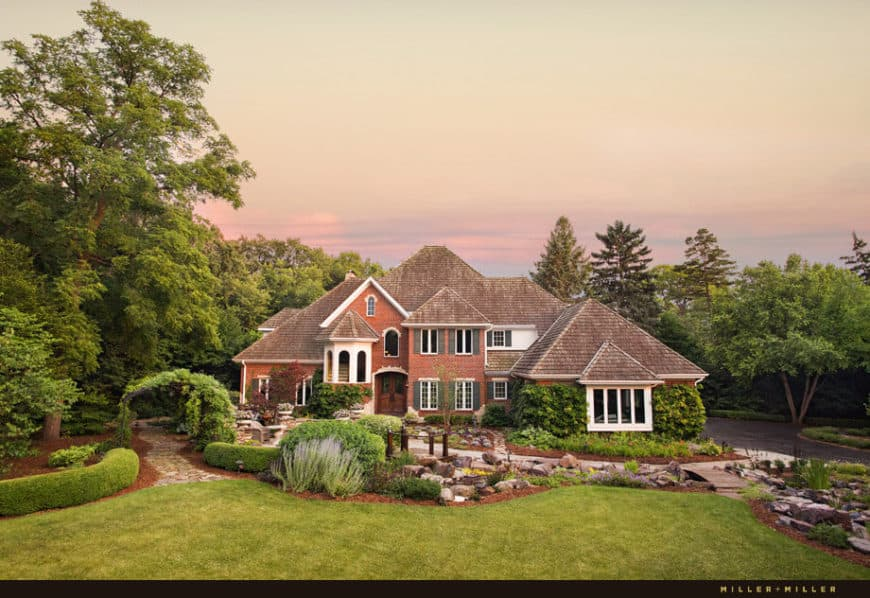 A luxurious custom home with a beautiful garden area and an elegant red exterior.