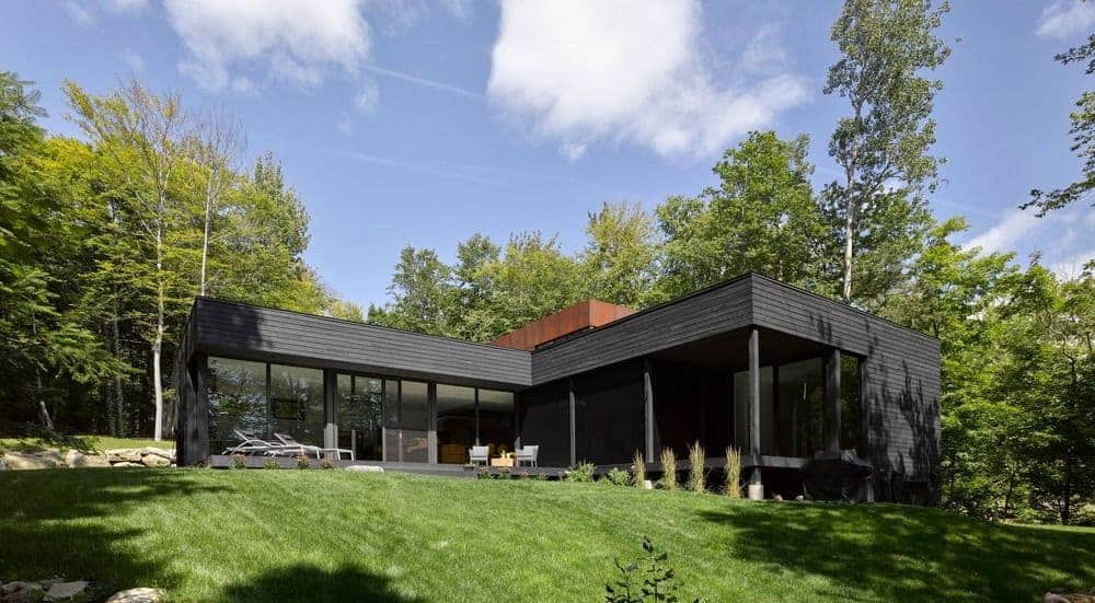 A black exterior modern house near the lake, set on the well-maintained lawns.
